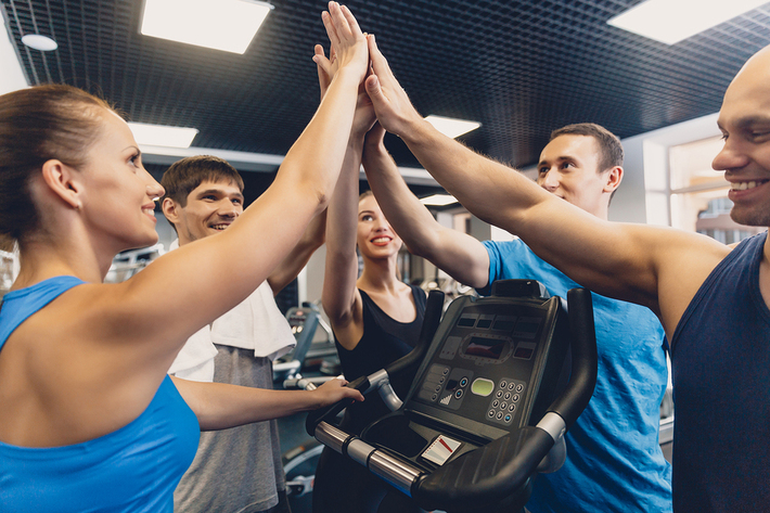 Group of people giving high-fives in a gym.