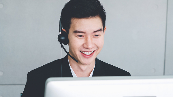 Wearing a headset in front of a computer.