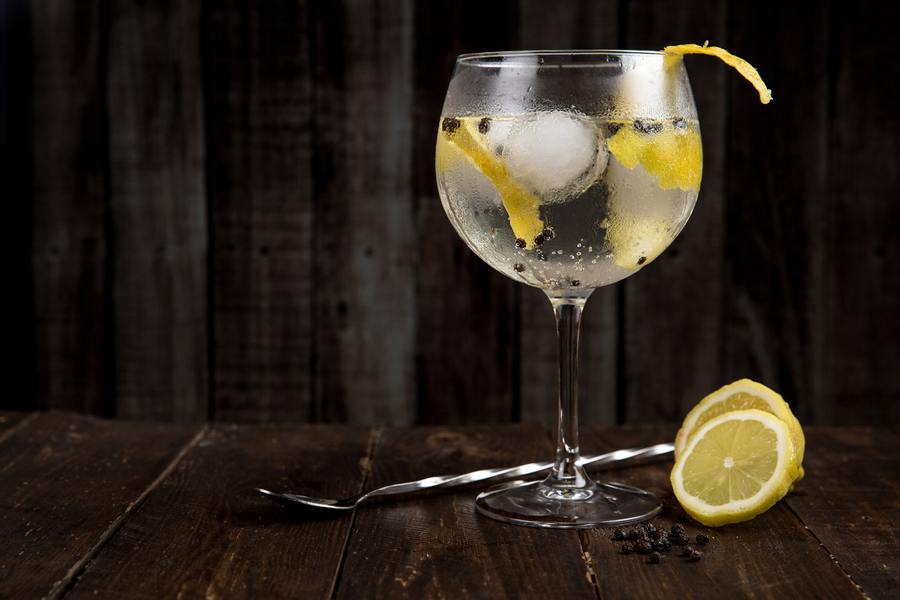 Alcohol drink in a glass with lemon.