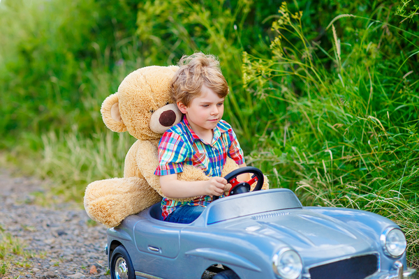 Young child driving a kid car with a teddybear behind him.