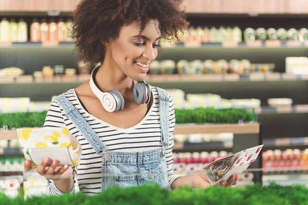 Woman grocery shopping with headphones.