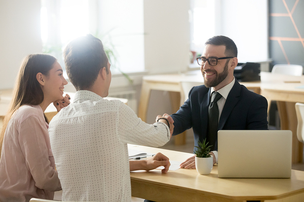 Couple shaking hands with a man in a business suit.