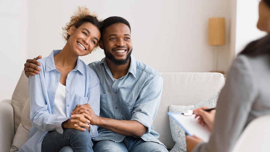 Smiling couple meeting with a therapist.