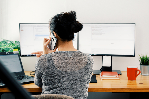 Woman talking on the phone in front of her computer.