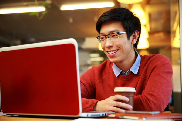 Young adult male looking at a laptop while drinking a cup of coffee.