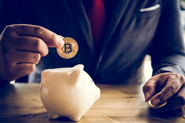 Placing a coin in a piggy bank.