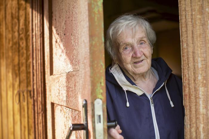 Elderly woman coming outside through a partially open door.