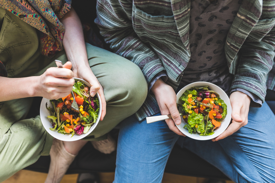 Two people sitting down eating healthy salads.