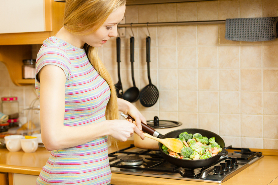 Woman cooking vegetables in a pan.