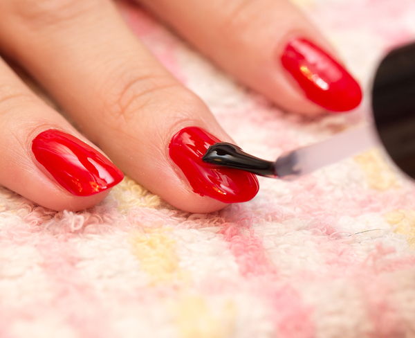 Woman having her fingernails painted red.