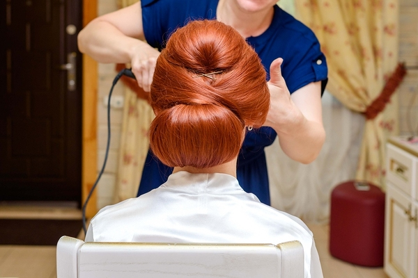 Woman with auburn hair getting her hair styled.