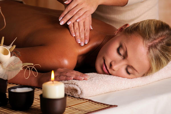 Woman lying down having a massage with a candle burning.
