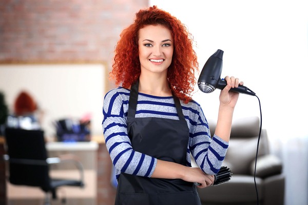 Woman with an apron in a beauty salon with a hair dryer smiling.