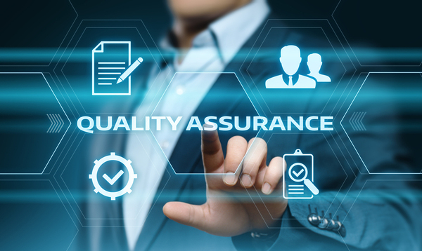 Man in a business suit pointing to the words quality assurance.