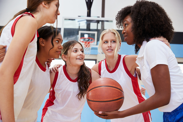 Five woman huddling together with a basketball.