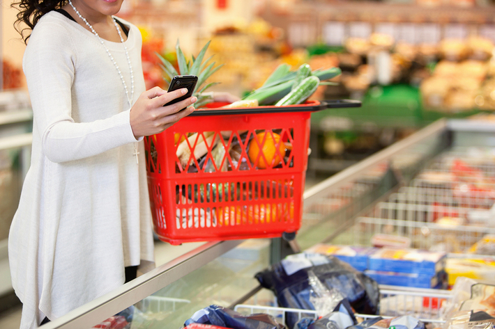 Woman shopping in a grocery store with a red basket.