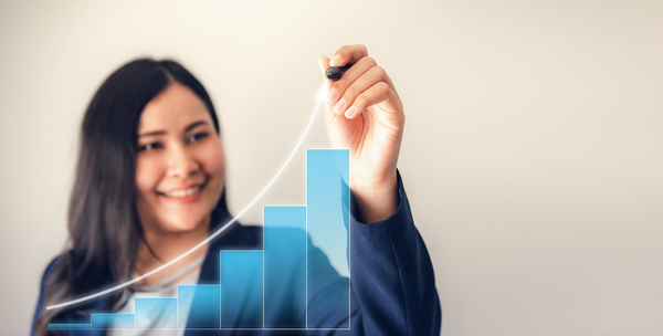 Woman drawing an upward trend line on a bar graph.